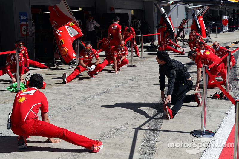 Ferrari mechanics stretching in the pitlane