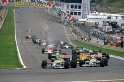 Nelson Piquet, Williams FW11B Honda and teammate Nigel Mansell, Williams FW11B Honda, lead Ayrton Senna, Lotus 99T Honda, at the start