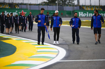 Pierre Gasly, Toro Rosso, and Sergio Perez, Force India, walk the circuit alongside colleagues