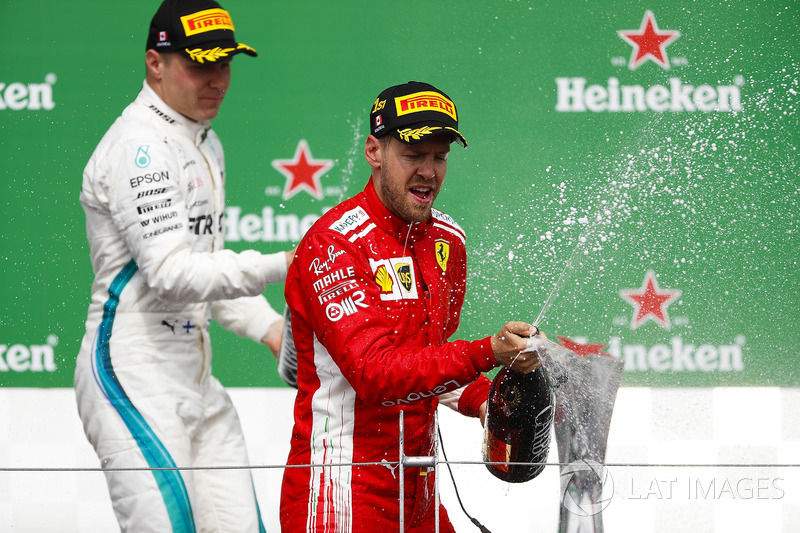 Valtteri Bottas, Mercedes AMG F1, 2nd position, and Sebastian Vettel, Ferrari, 1st position, spray Champagne on the podium