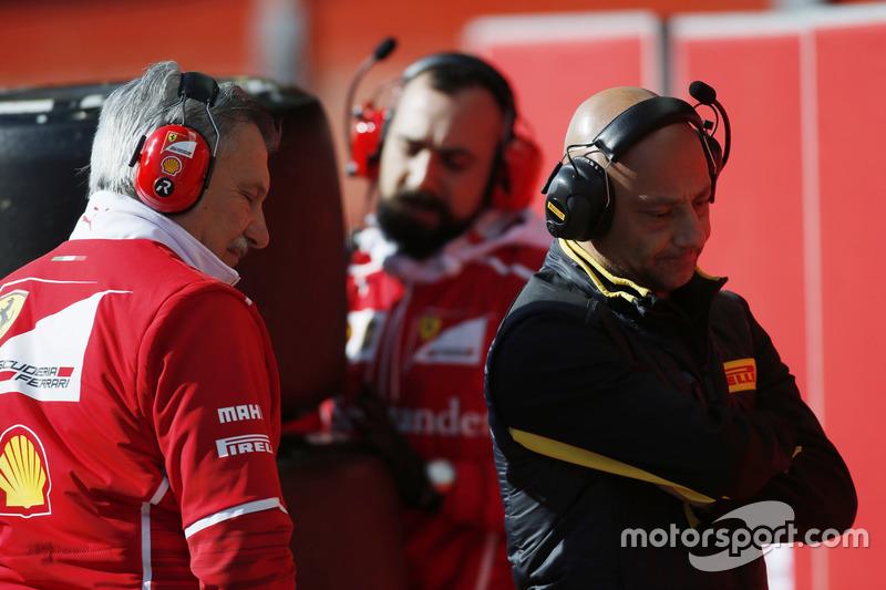 Ferrari team members push a stack of tyres past a Pirelli employee