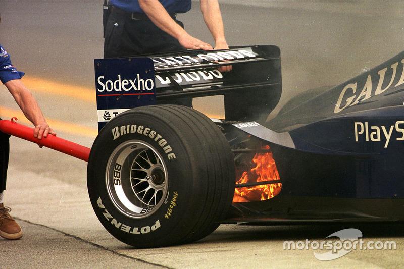 Prost mecánicos con un pequeño fuego durante el calientamiento para el gran premio de Japón.