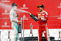 (L to R): Race winner Nico Rosberg, Mercedes AMG F1 celebrates with the champagne on the podium with