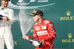 Lewis Hamilton, Mercedes AMG, 2nd Position, and Sebastian Vettel, Ferrari, 1st Position, spray Champagne on the podium