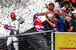 Winnaar Lewis Hamilton, Mercedes AMG F1 op het podium met champagne en de fans