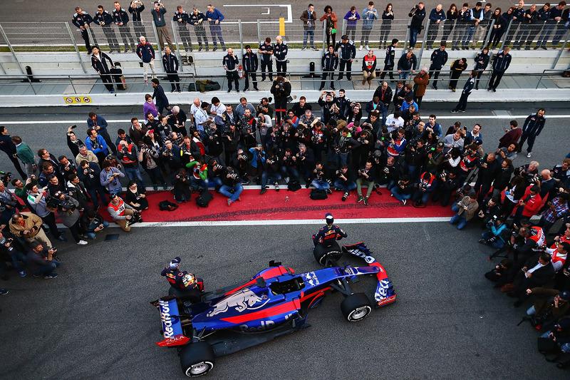 Гонщики Scuderia Toro Rosso Даниил Квят и Карлос Сайнс-мл. позируют рядом с автомобилем STR12