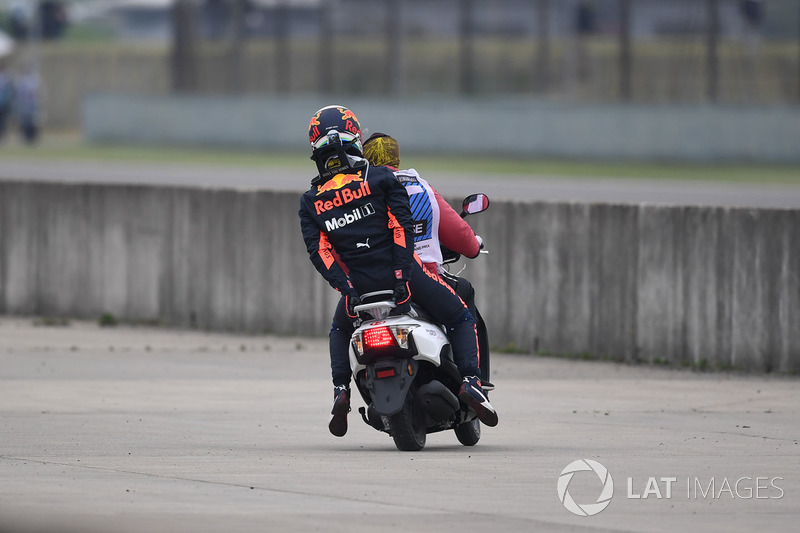 Daniel Ricciardo, Red Bull Racing stopped on track in FP3 and catches a lift on a scooter