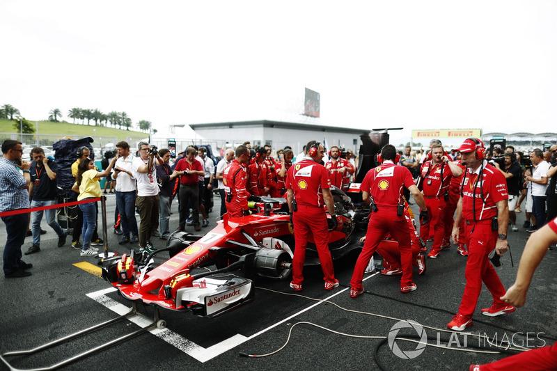 The Ferrari team frantically try to fix the Kimi Raikkonen Ferrari SF70H on the grid, Journalist Jonathan Noble looks on it