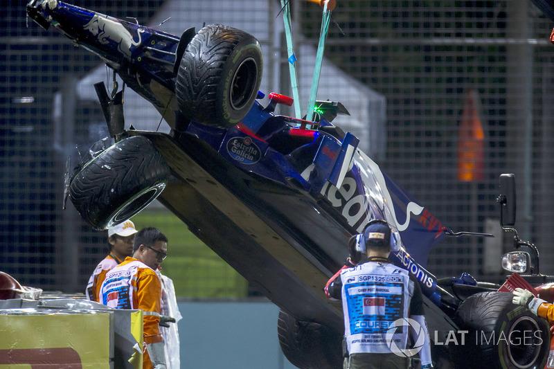 Marshals supervise a crane removing the wrecked Daniil Kvyat Scuderia Toro Rosso STR12