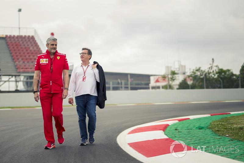 Maurizio Arrivabene, Ferrari director del equipo y Louis Camilleri, presidente de Philip Morris caminan por la pista