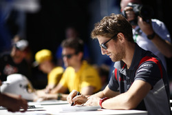 Romain Grosjean, Haas F1 Team, signs autographs alongside Jolyon Palmer, Renault Sport F1 Team