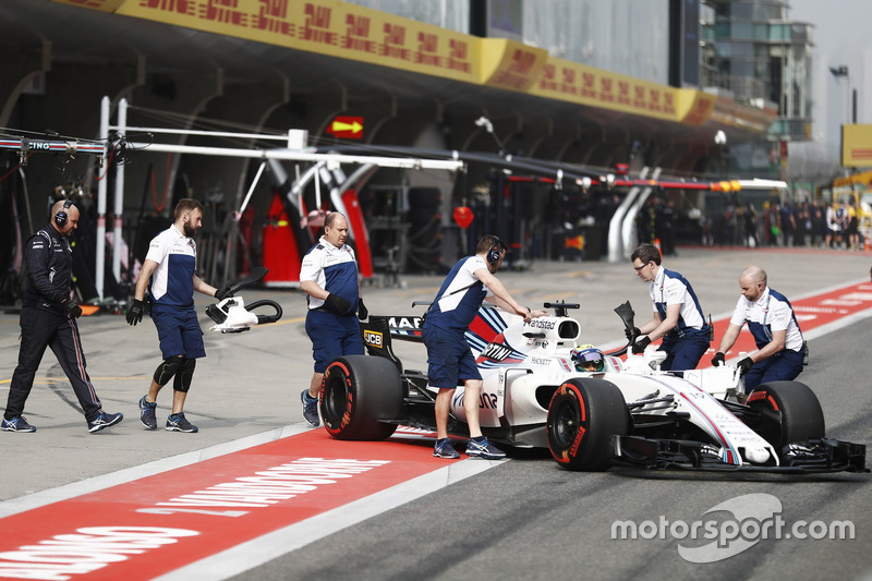 The Williams team return Felipe Massa, Williams FW40, to the garage