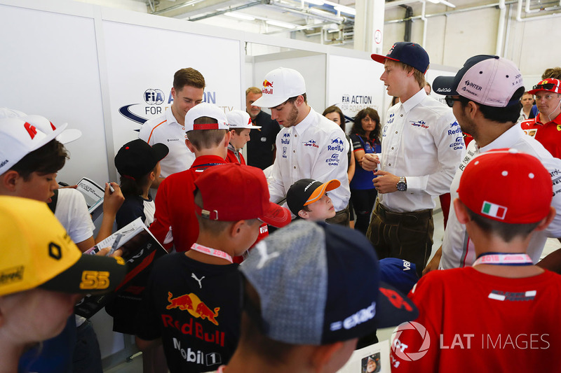 Pierre Gasly, Toro Rosso, and Brendon Hartley, Toro Rosso, wear traditional Austrian costume as they sign autographs