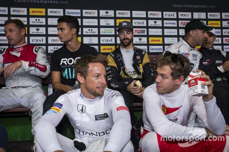Jenson Button y Sebastian Vettel, hablar durante los pilotos reciben información backstage