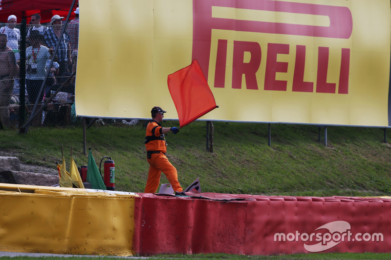 A marshal waves a red flag as the race is stoppd
