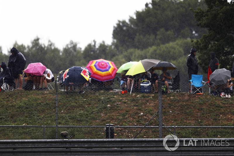 Spectators shelter from the rain under umbrellas
