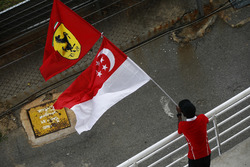 A fan waves flags in support of Singapore and Ferrari