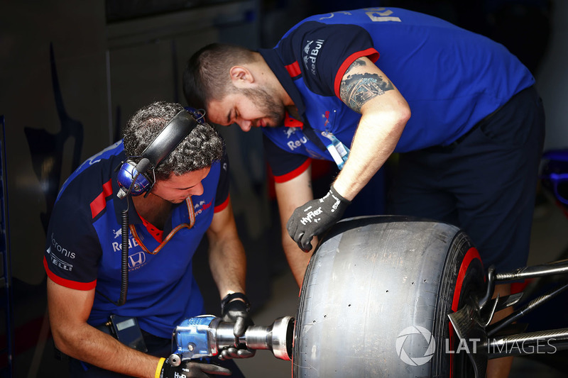 Toro Rosso team members change a wheel