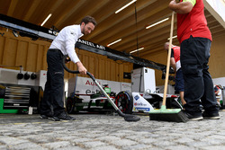 An Audi team member hoovers the cobbled pit garage