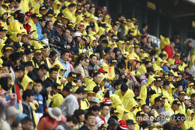 Crowds in yellow Pirelli macs in the grandstands