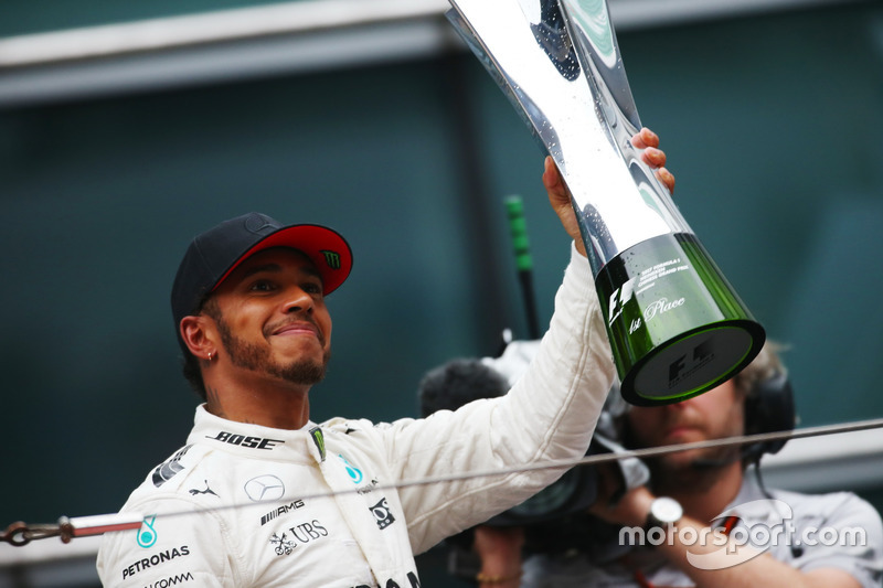 Lewis Hamilton, Mercedes AMG, lifts his trophy on the podium