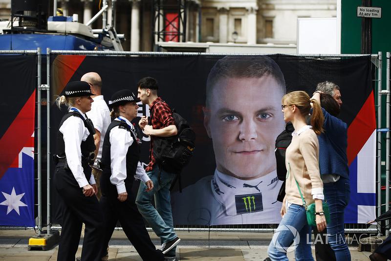 Police Officers walk past a portrait of Valtteri Bottas, Mercedes AMG F1