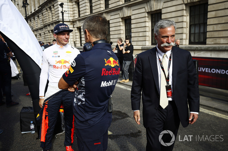 Chase Carey, Chairman, Formula One, walks past Max Verstappen, Red Bull