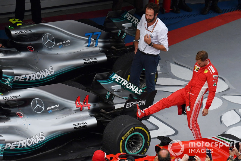 Sebastian Vettel, Ferrari looks at the rear Pirelli tyre of the car of Lewis Hamilton, Mercedes-AMG F1 W09 in parc ferme