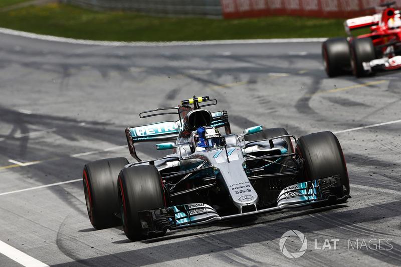 Valtteri Bottas, Mercedes AMG F1 W08, lifts his arm in victory celebration at the finish, ahead of Sebastian Vettel, Ferrari SF70H