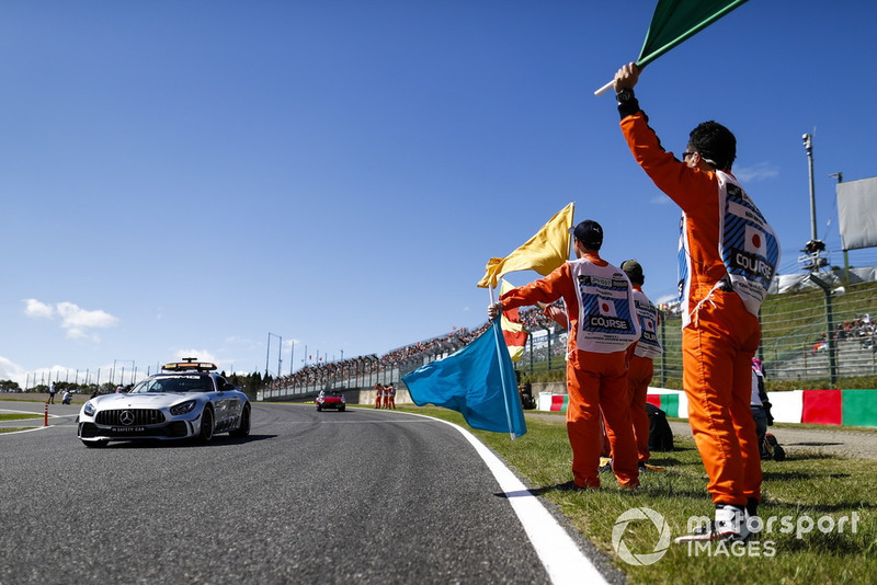 Marshals wave flags as the Safety Car passes ahead of the drivers parade
