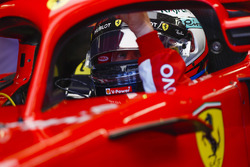 Kimi Raikkonen, Ferrari, in cockpit, reaches towards his halo