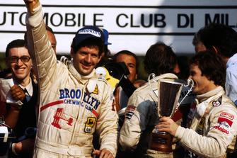 Race winner and World Championship Jody Scheckter, celebrates on the podium with Gilles Villeneuv, Ferrari