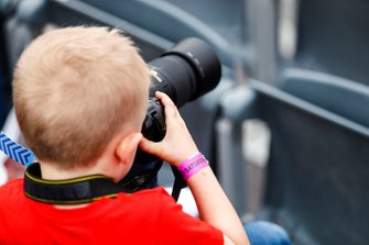 A fan in the grandstand takes photos on the track action