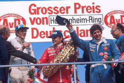 Niki Lauda, 1st position, Jody Scheckter, 2nd position and Hans-Joachim Stuck, 3rd position on the podium