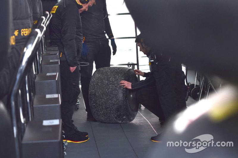Kru Pirelli dan McLaren memeriksa ban kanan-belakang yang terlepas dari mobil Fernando Alonso