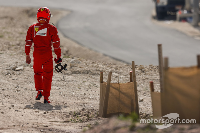 Kimi Raikkonen, Ferrari, walks back to the garage