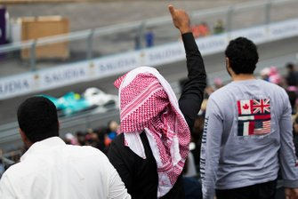 A fan gives a thumbs up to the on track action