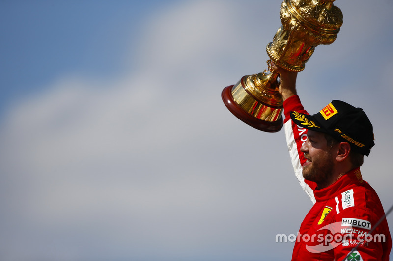 Sebastian Vettel, Ferrari, celebrates victory on the podium, and raises his trophy