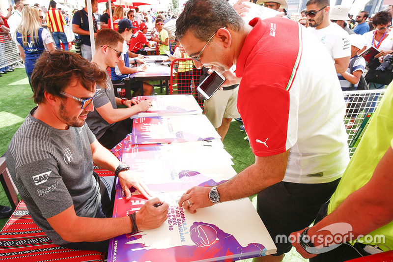 Fernando Alonso, McLaren, signs autographs for fans