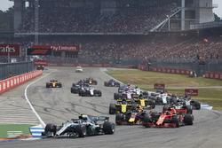 Valtteri Bottas, Mercedes AMG F1 W09, leads Kimi Raikkonen, Ferrari SF71H, Max Verstappen, Red Bull Racing RB14, Romain Grosjean, Haas F1 Team VF-18, Nico Hulkenberg, Renault Sport F1 Team R.S. 18, and the remainder of the field at the start