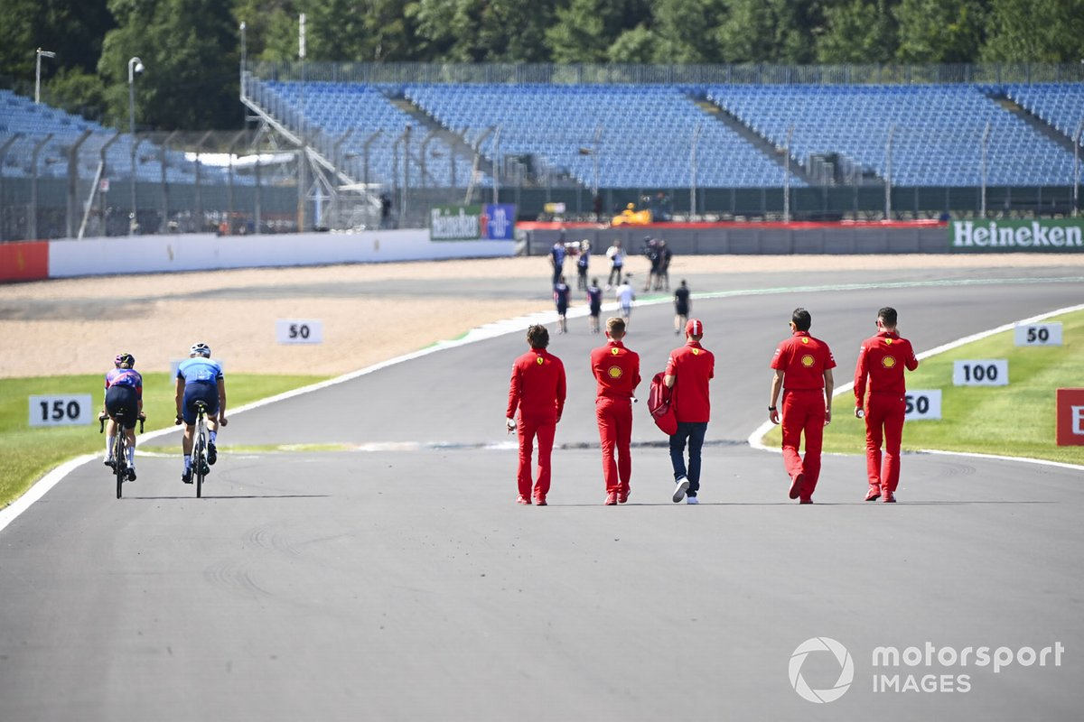 Valtteri Bottas, Mercedes-AMG Petronas F1 and Tiffany Cromwell cycle the track past Sebastian Vettel, Ferrari as he walks the track with his engineers