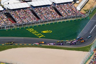 Nico Hulkenberg, Renault F1 Team R.S. 19, leads Romain Grosjean, Haas F1 Team VF-19, Kimi Raikkonen, Alfa Romeo Racing C38, Lando Norris, McLaren MCL34, Sergio Perez, Racing Point RP19, and the remainder of the field through the first corner