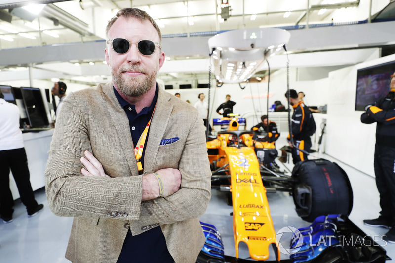 Guy Ritchie poses for a picture with the car of Stoffel Vandoorne, McLaren MCL33 Renault