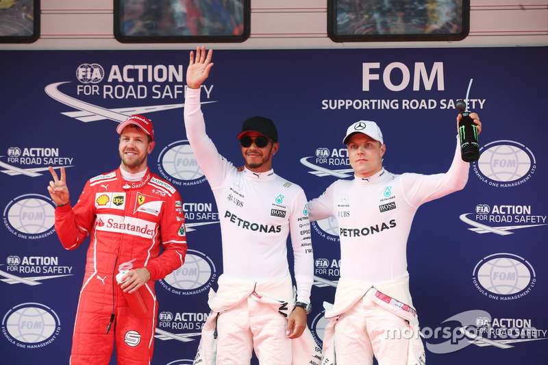 Lewis Hamilton, Mercedes AMG, celebrates taking pole position alongside Sebastian Vettel, Ferrari an