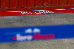 Pit-lane wording painted onto the pit lane road outside of the Scuderia Toro Rosso garage