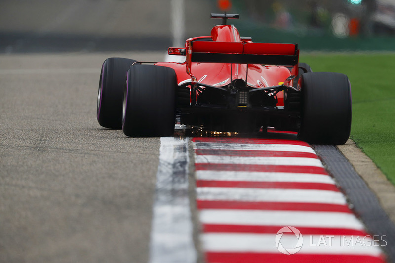 Sebastian Vettel, Ferrari SF71H, strikes up sparks over a kerb