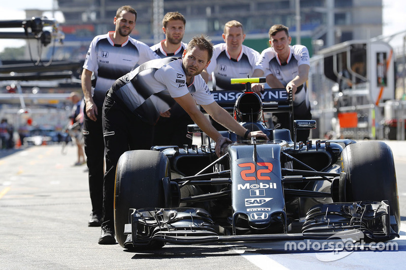 McLaren team members wheel the McLaren MP4-31 Honda of Jenson Button in the pit lane