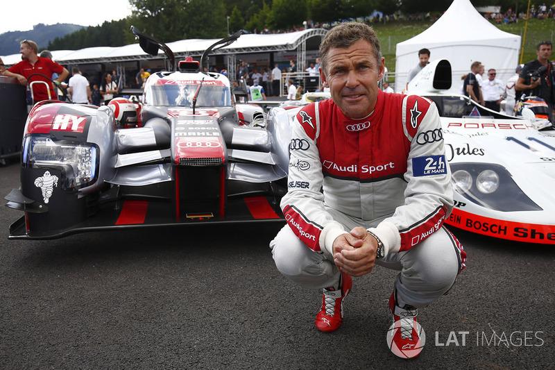 Tom Kristensen poses between an Audi LMP1 and Porsche 936