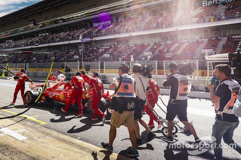 Механики толкают по пит-лейну Ferrari SF70H Себастьяна Феттеля
