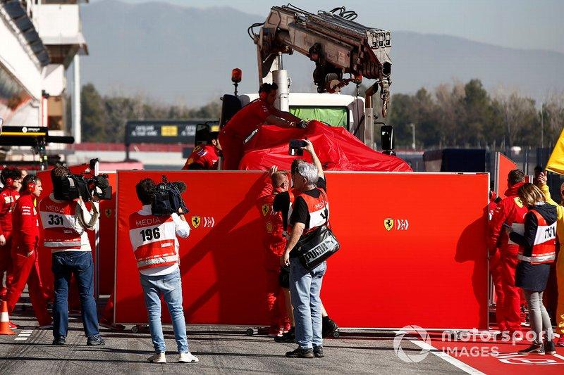 The car of Sebastian Vettel, Ferrari SF90 is revovered to the garage shielded by screens